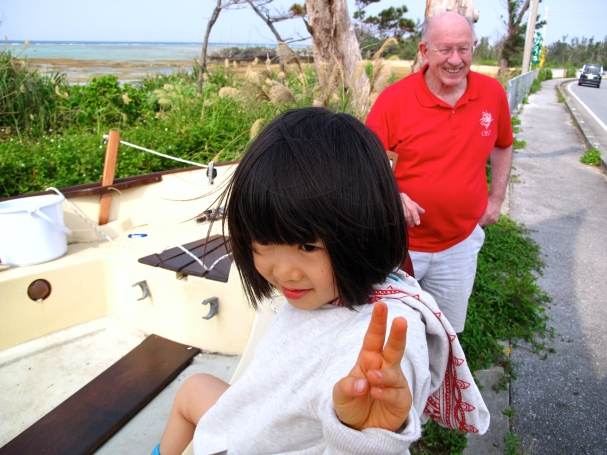 A little girl comes by and wants to sit in the boat.